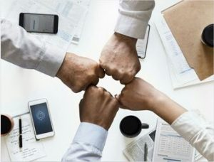 Picture of four fists with forearms wearing light colored dress shirts coming together over a meeting table that has mobile phones, notepads, coffee cups, and folders.