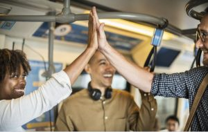 two people on a subway high-fiving